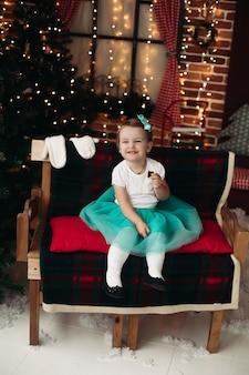 Mooi klein meisje, zittend op een houten bank bedekt met plaid