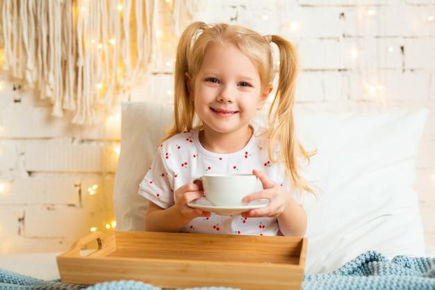 Mooi klein meisje, zittend op het bed met een kopje thee