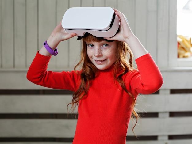 Mooi klein roodharig meisje lacht en houdt een display op het hoofd