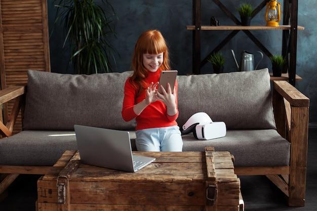 Mooi klein roodharig meisje zittend op de bank in de kamer en flipping smartphone