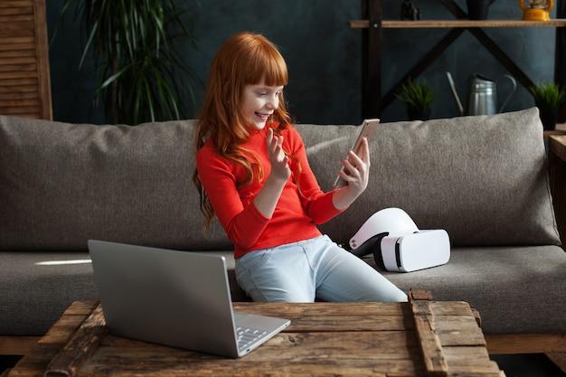 Mooi klein roodharig meisje zittend op een bank in de kamer en kijken naar smartphone scherm
