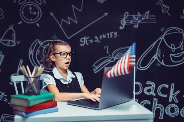 Mooi klein schoolmeisje bij bureau tegen zwarte achtergrond met de vlag van de v.s