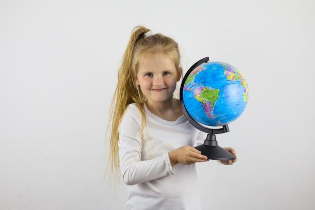 Mooi klein schoolmeisjemeisje dat een bol houdt. het concept van nieuwe kennis. het nieuwe schooljaar