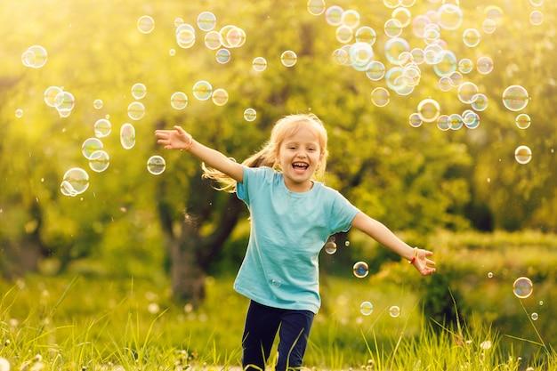 Mooi kleinharig haarmeisje, heeft een blij lachend gezicht, mooie ogen, kort haar, speelt zeepbellen, gekleed in een t-shirt. kind portret. .