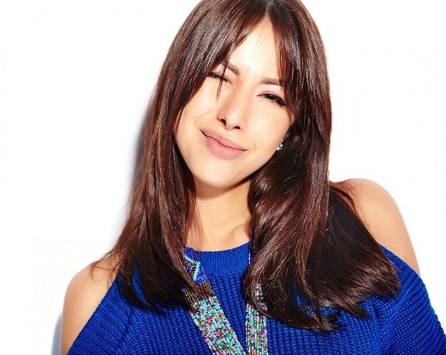 Mooi knipogend hipster donkerbruin vrouwenmodel in toevallige modieuze de zomer blauwe sweater die op witte achtergrond wordt geïsoleerd