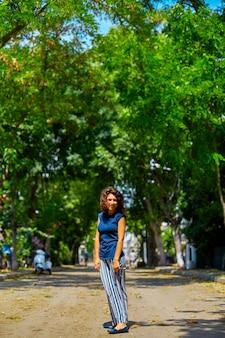 Mooi krullend brunette meisje model wandelingen op een zomerdag