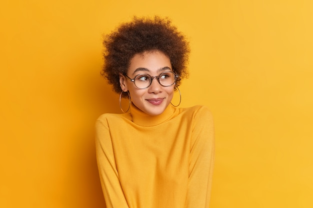 Mooi krullend haar meisje kijkt opzij met blije uitdrukking draagt casual coltrui transprent bril bewondert iets moois voelt zich gelukkig.