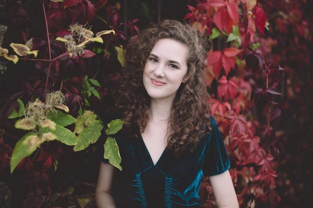 Mooi krullend haarmeisje in een donkerblauwe fluweelkleding in een de herfstpark