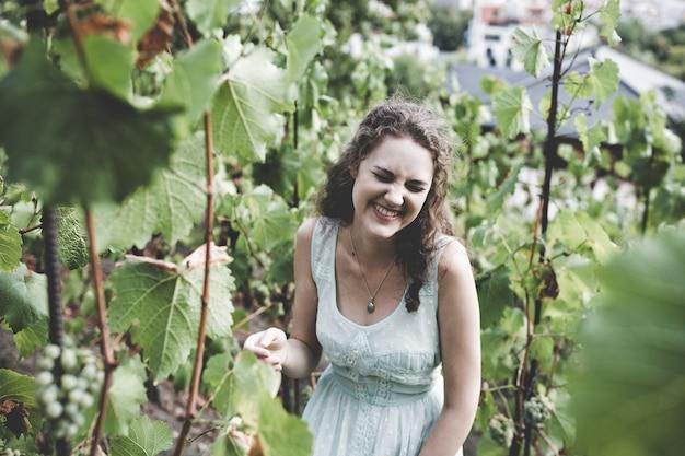Mooi krullend haarmeisje in een lichtblauwe eenvoudige kleding in een wijngaard