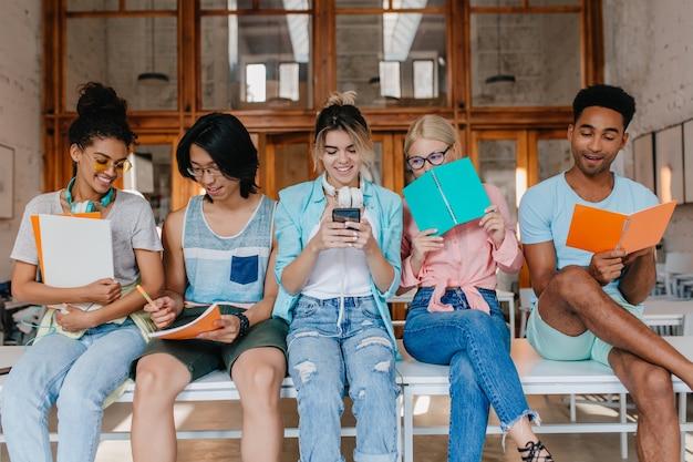 Mooi krullend meisje dat in oortelefoons kijkt wat haar aziatische vriend toont, die omslagen houdt. binnenportret van studenten met notitieboekjes die examens in bibliotheek bespreken.