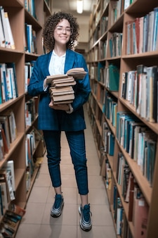 Mooi krullend meisje in glazen en een blauw pak staat in de bibliotheek
