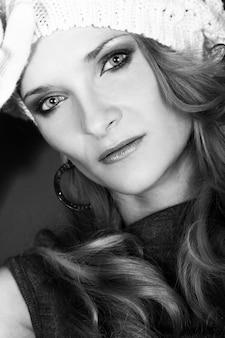Mooi krullend meisje in witte hoed en handschoenen
