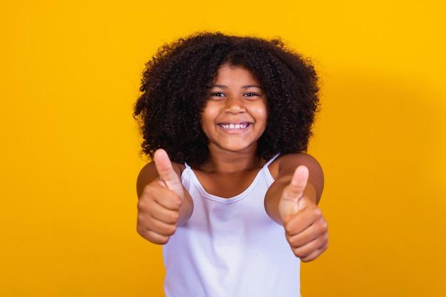 Mooi krullend meisje met haar handen ok teken. gele achtergrond. afro meisje ok duim omhoog