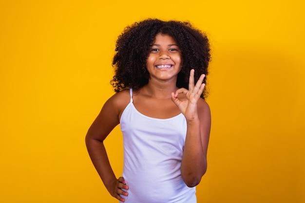 Mooi krullend meisje met haar handen ok teken. gele achtergrond. afro vrouw oke