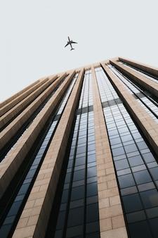 Mooi laag hoekschot van een lang bedrijfsgebouw met een vliegtuig dat boven vliegt