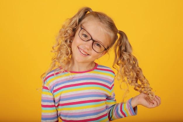 Mooi lachend blond meisje met een bril op een gele achtergrond in een gekleurd jasje