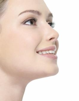 Mooi lachend gezicht van vrouw close-up in profiel op wit