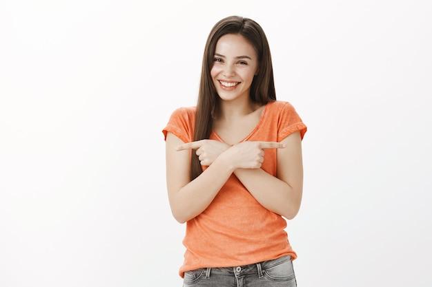 Mooi lachend meisje dat zijwaarts richt, twee producten toont en gelukkig glimlacht