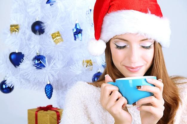 Mooi lachend meisje in de buurt van kerstboom met cup