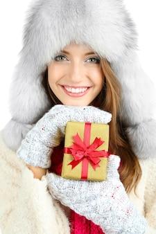 Mooi lachend meisje in hoed met kerstcadeau geïsoleerd op wit
