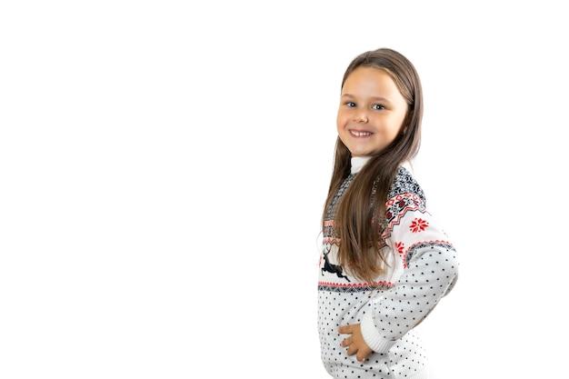 Mooi lachend meisje in witte gebreide kersttrui met rendieren geven met handen in taille i...
