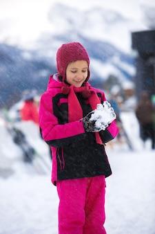 Mooi lachend meisje poseren tegen hoge bergen met sneeuwbal