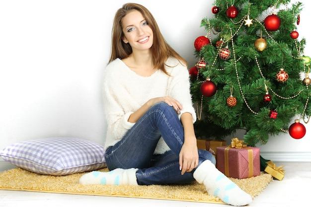 Mooi lachend meisje zit in de buurt van de kerstboom in de kamer