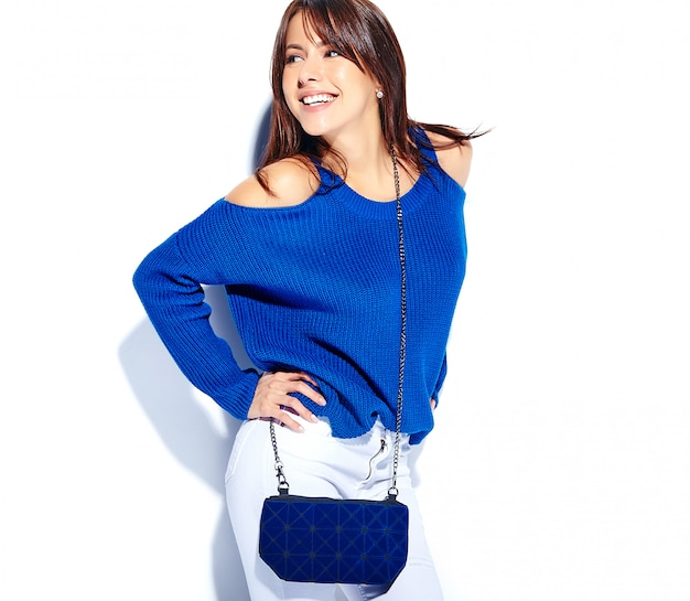 Mooi lachende hipster brunette vrouw model in casual stijlvolle zomer trui en blauwe handtas geïsoleerd op een witte achtergrond
