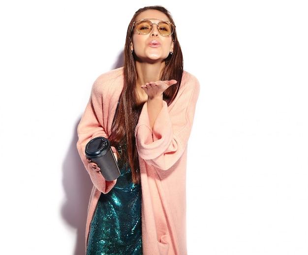 Mooi lachende hipster brunette vrouw model in stijlvolle roze overjas. koffie drinken en een kus geven