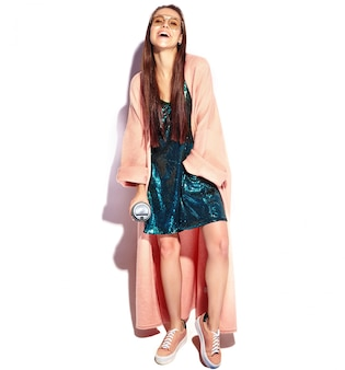 Mooi lachende hipster brunette vrouw model in stijlvolle roze overjas. koffie drinken, volledige lengte