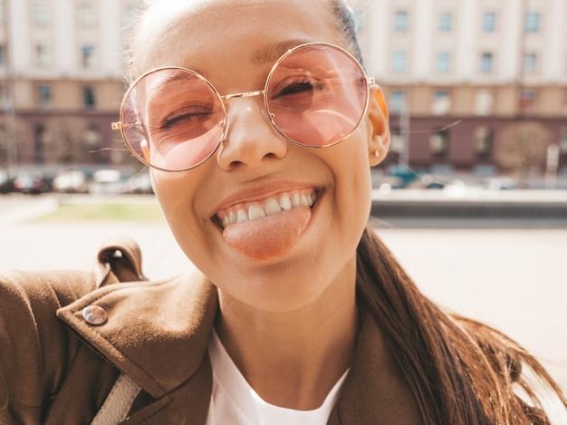 Mooi lachende meisje in zomer hipster jas en jeans. model nemen selfie op smartphone. vrouw maken van foto's in de straat. zittend op de bank in zonnebril en tong tonen