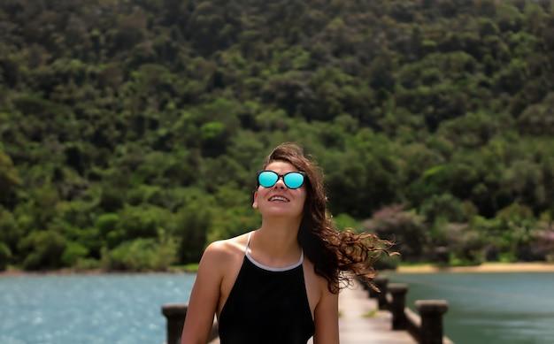 Mooi lachende meisje in zonnebril met krullend haar opzoeken op de pier bij de oceaan.