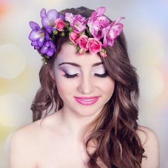 Mooi lachende meisje met bloemen in haar haar