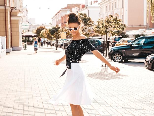 Mooi lachende model gekleed in elegante zomer kleding. sexy zorgeloos meisje dansen in de straat. trendy moderne zakenvrouw in zonnebril plezier in beweging