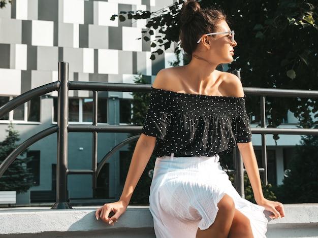 Mooi lachende model gekleed in elegante zomer kleding. sexy zorgeloos meisje zit in de straat. trendy moderne zakenvrouw in zonnebril plezier