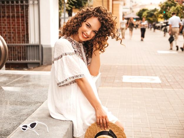 Mooi lachende model met afro krullen kapsel gekleed in zomer hipster witte jurk.