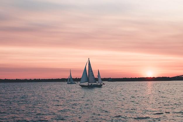 Mooi landschap dat van zeilboten in het overzees onder roze hemel is ontsproten