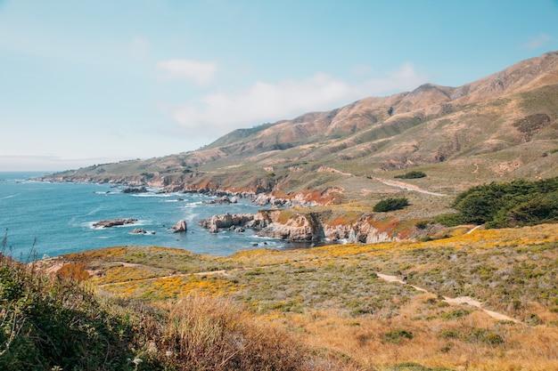 Mooi landschap dichtbij monterey-stad in californië. turkooise oceaan met grote golven en rotswanden. paradise beach van californië. stille oceaan en kliffen met planten.
