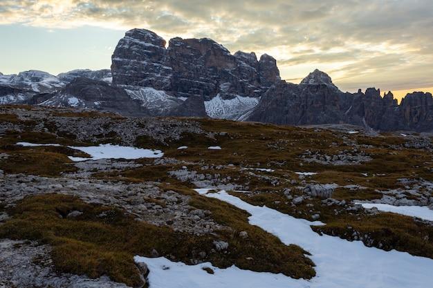 Mooi landschap in de italiaanse alpen onder de bewolkte hemel tijdens de zonsondergang