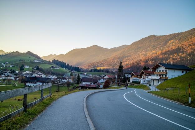 Mooi landschap met asfaltweg door het traditionele land in oostenrijk op een achtergrond van bergen en heldere blauwe hemel op een zonnige dag.