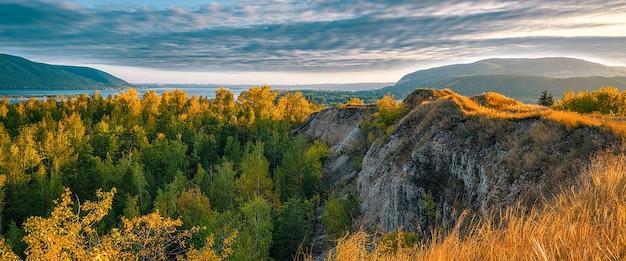 Mooi landschap met bergen en heuvels, rivier en bos met bewolkte hemel.