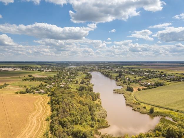 Mooi landschap met landbouwvelden, land en brede rivier op een achtergrond van blauwe bewolkte hemel in een zonnige zomerdag. luchtfoto van drone.