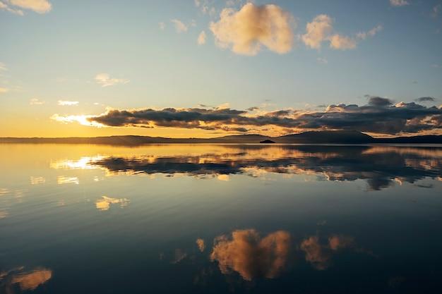 Mooi landschap met reflecties in het water van de blauwe lucht en de wolken met het gele zonlicht bij dageraad.