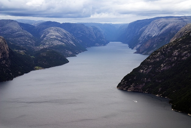 Mooi landschap van beroemde kliffen preikestolen in de buurt van een meer onder een bewolkte hemel in stavanger, noorwegen