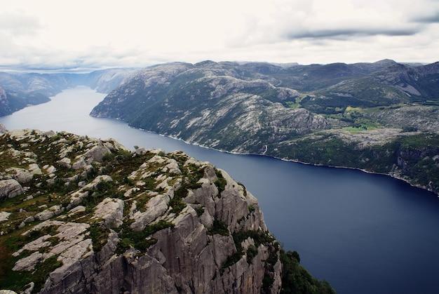 Mooi landschap van de beroemde kliffen preikestolen in de buurt van een rivier onder een bewolkte hemel in stavanger, noorwegen