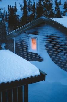 Mooi landschap van dorp met houten hutten bedekt met sneeuw, omringd door sparren in noorwegen