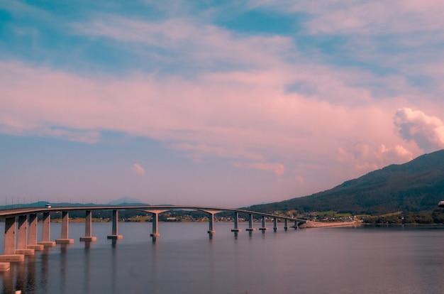 Mooi landschap van een betonnen brug over het meer in de buurt van hooggebergte tijdens zonsondergang in noorwegen