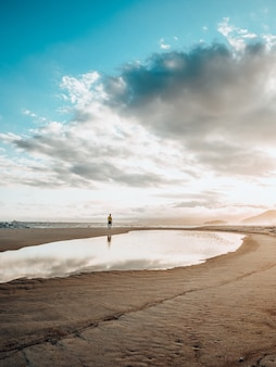 Mooi landschap van een solo-persoon die traint tijdens de zonsondergang op het strand met een bewolkte hemel