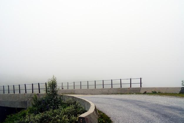 Mooi landschap van een weg op een sombere dag met een mistige achtergrond in noorwegen