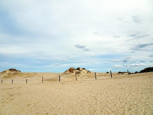 Mooi landschap van een zandstrand onder een bewolkte hemel in leba, polen